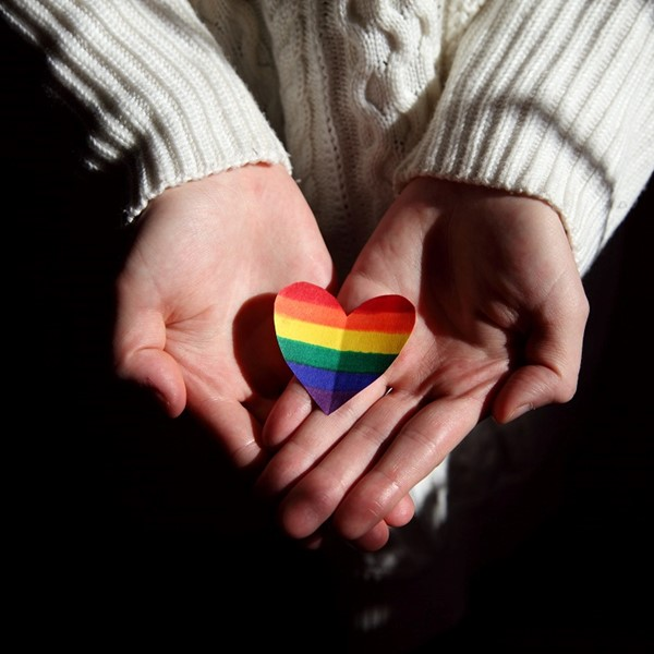 Woman holding heart painted in LGBTQ flag colors.