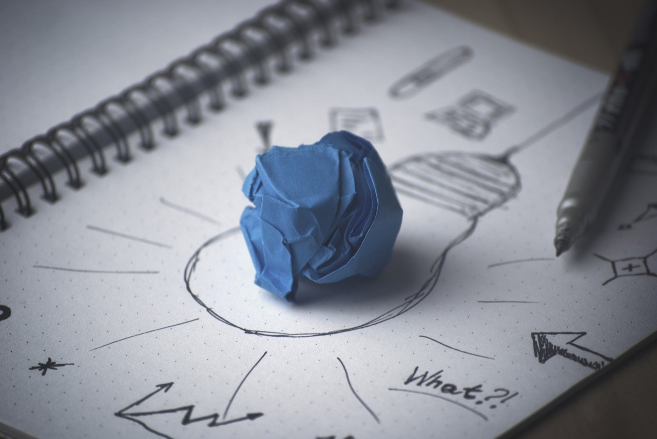A crumpled paper ball over a book with bulb drawing.