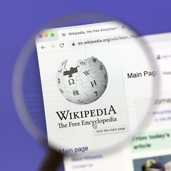 Wikipedia website under a magnifying glass.